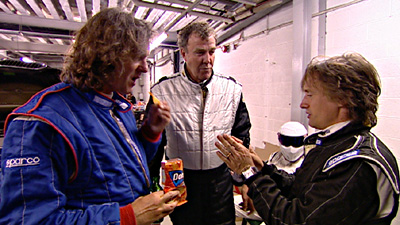 top gear hosts: Jeremy Clarkson, James May, Richard Hammond and the Stig sitting in the background